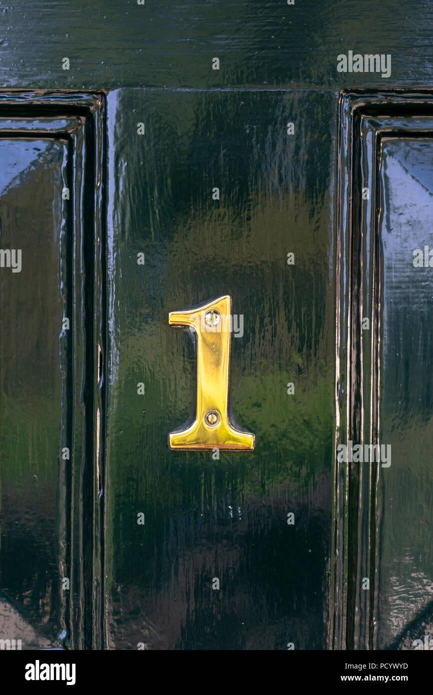 Brass number 1on dark green door - Stock Image