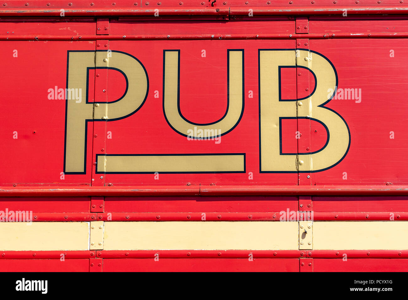 The word Pub in gold on red background - Stock Image