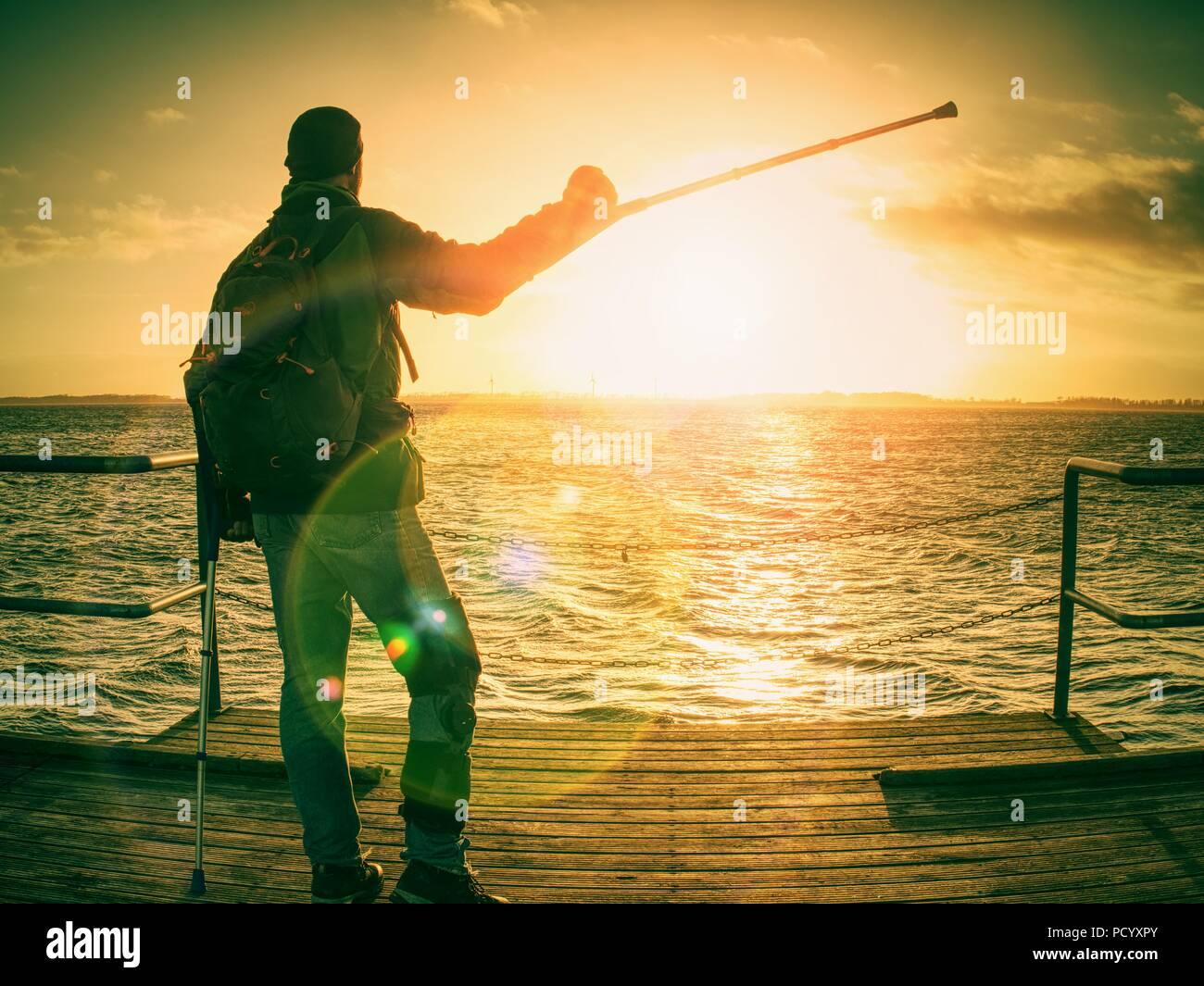 Hiker with medicine crutch and leg fixed in immobilizer walk on wharf pier. Man has fixed broken leg in plaster. Happy disabled man on beach walk. Len - Stock Image