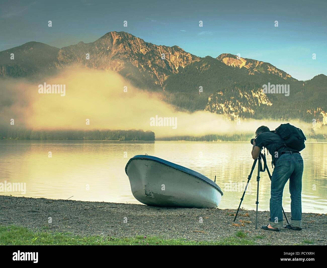 Man hiker is taking photo of ship at mountain lake shore. Silhouette at fishing paddle boat at lake coast. - Stock Image