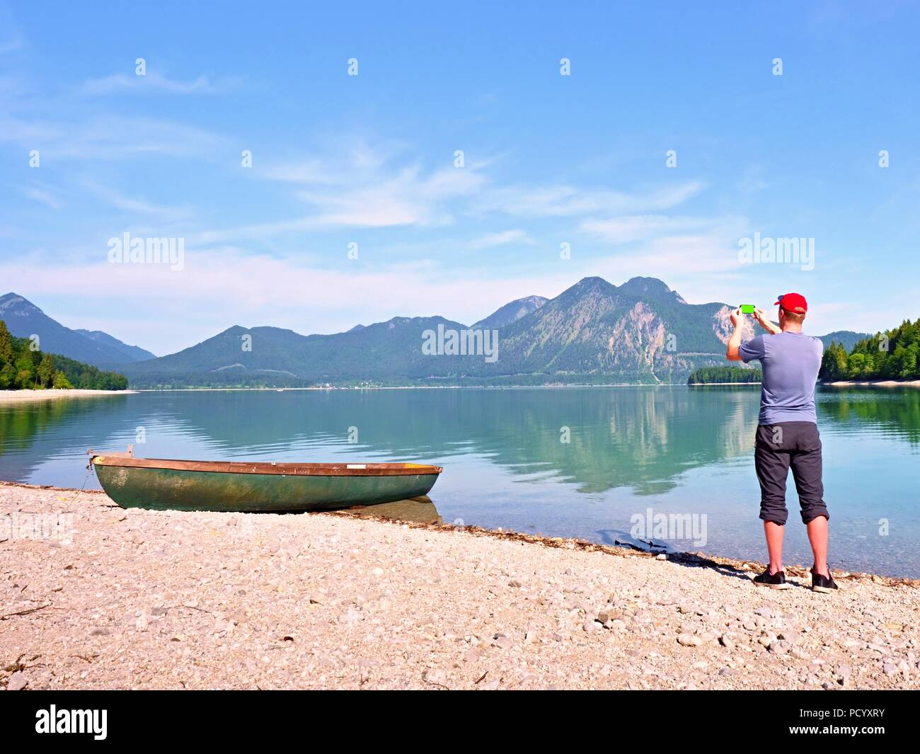 Man hiker is taking photo of ship at mountain lake shore. Silhouette at fishing paddle boat at lake coast. - Stock Image