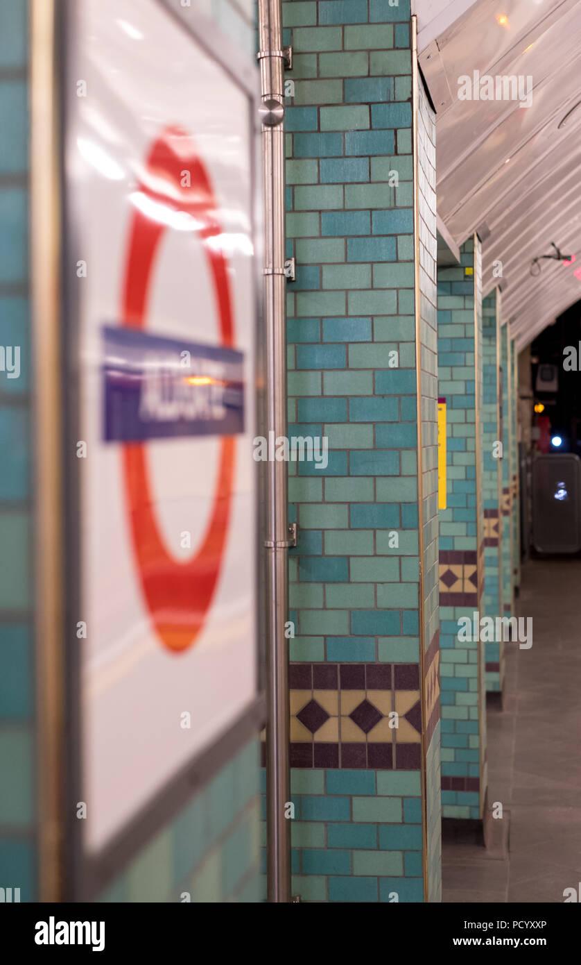 Platform at Aldgate Underground Station, London showing station name in TFL roundel. - Stock Image