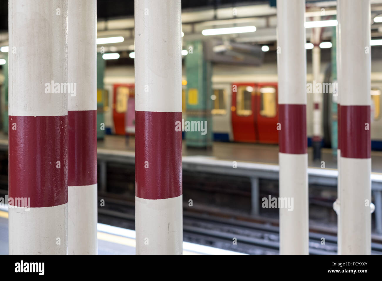 Platform at Aldgate Underground Station, London showing painted pillars and train in soft focus waiting on platform in the background. - Stock Image