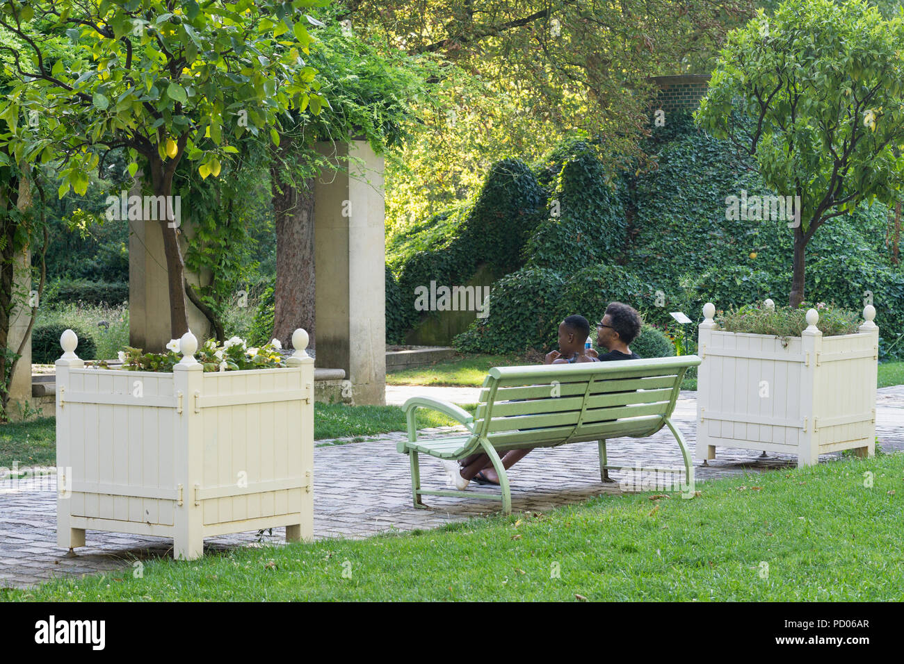 A couple sitting on bench in the Park Bercy in the 13th arrondissement of Paris, France. - Stock Image