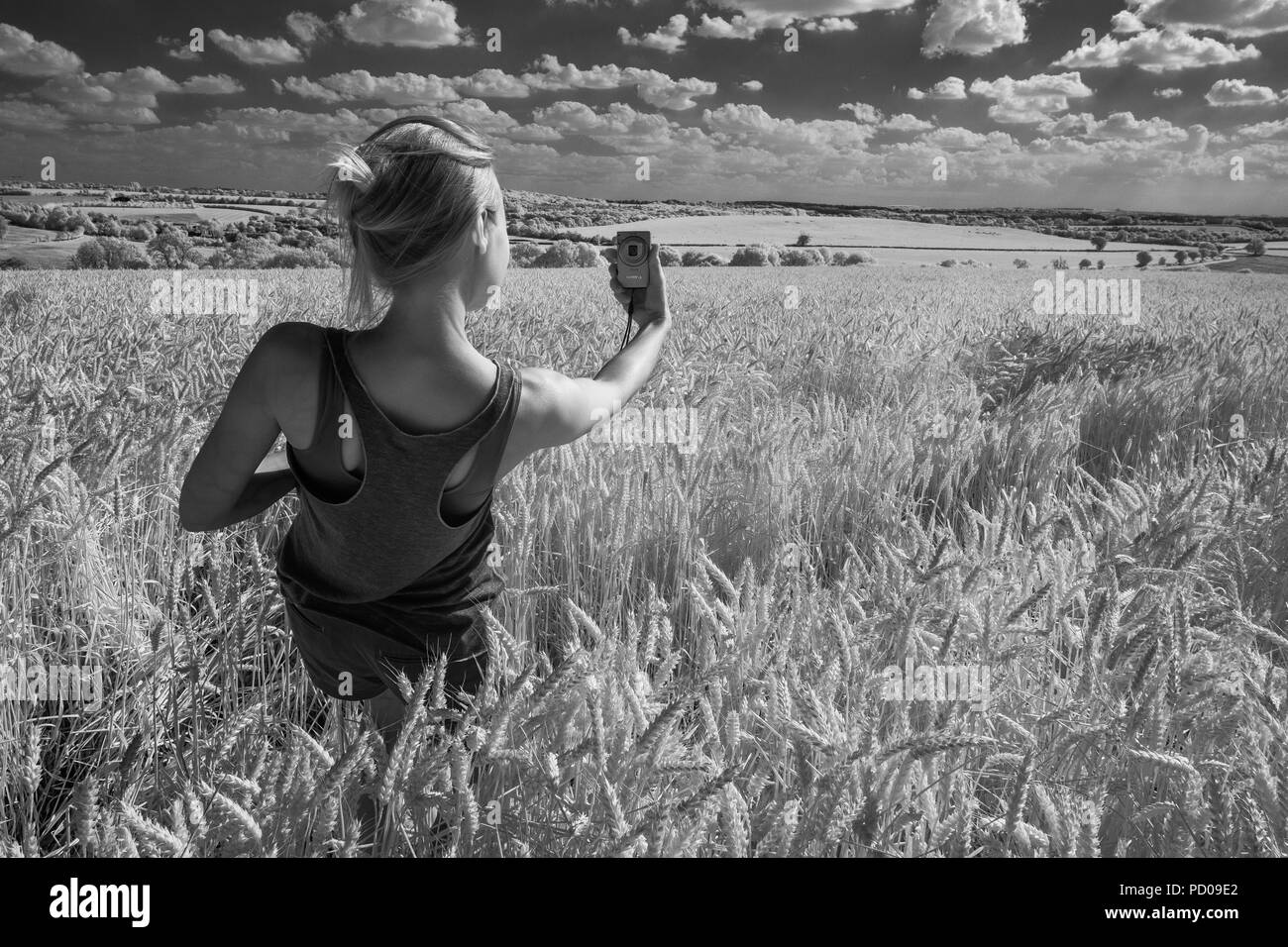 Young woman taking a photo of herself. - Stock Image
