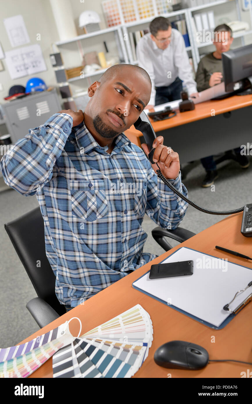 man on the phone with aching back - Stock Image