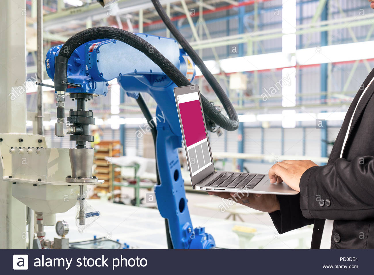 Maintenance engineer using laptop computer control automatic robotic hand with CNC machine in smart factory, Industry 4.0 concept - Stock Image