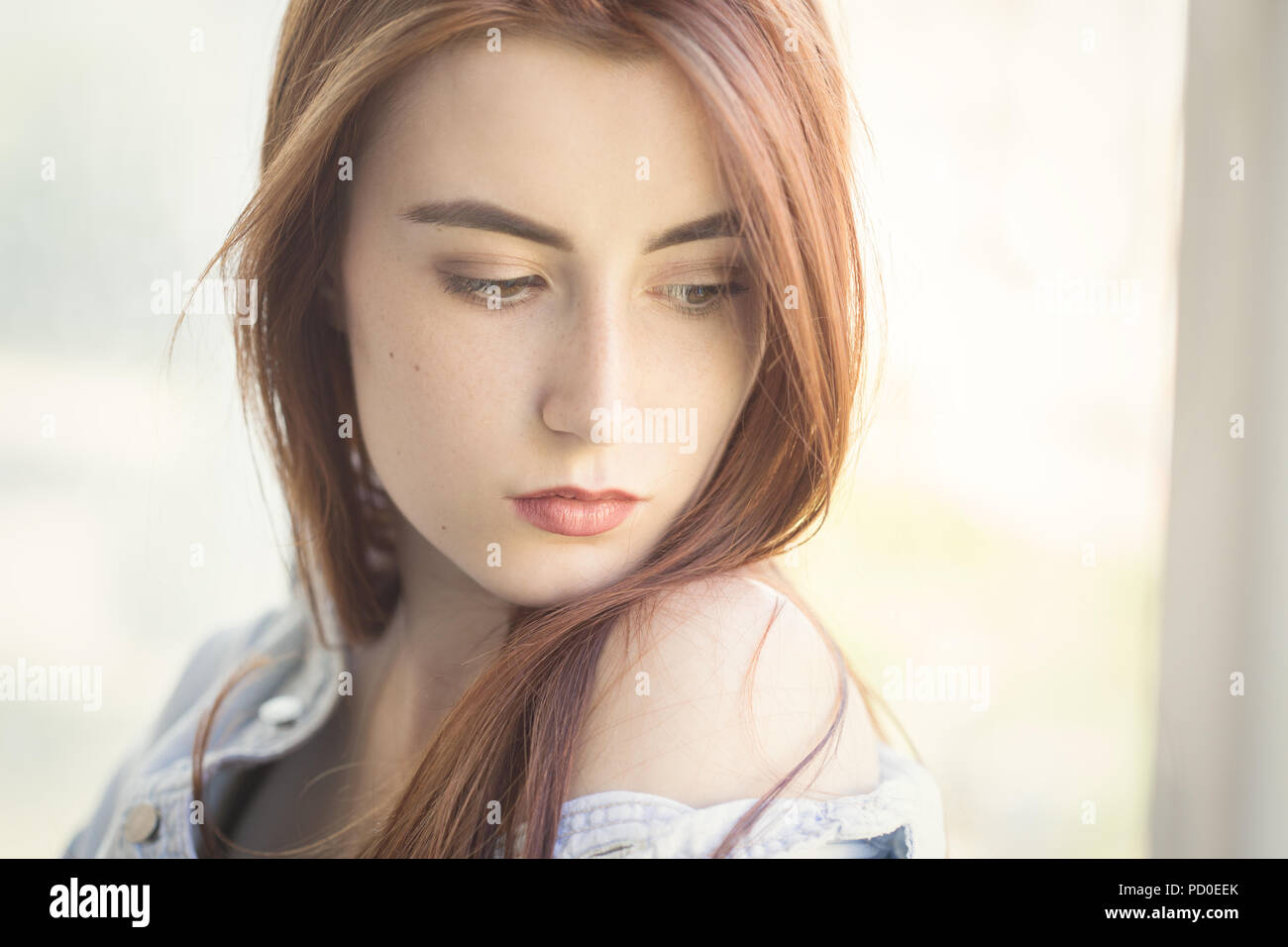 pensive woman with red hair and bare shoulder thinker near window looking aside - Stock Image