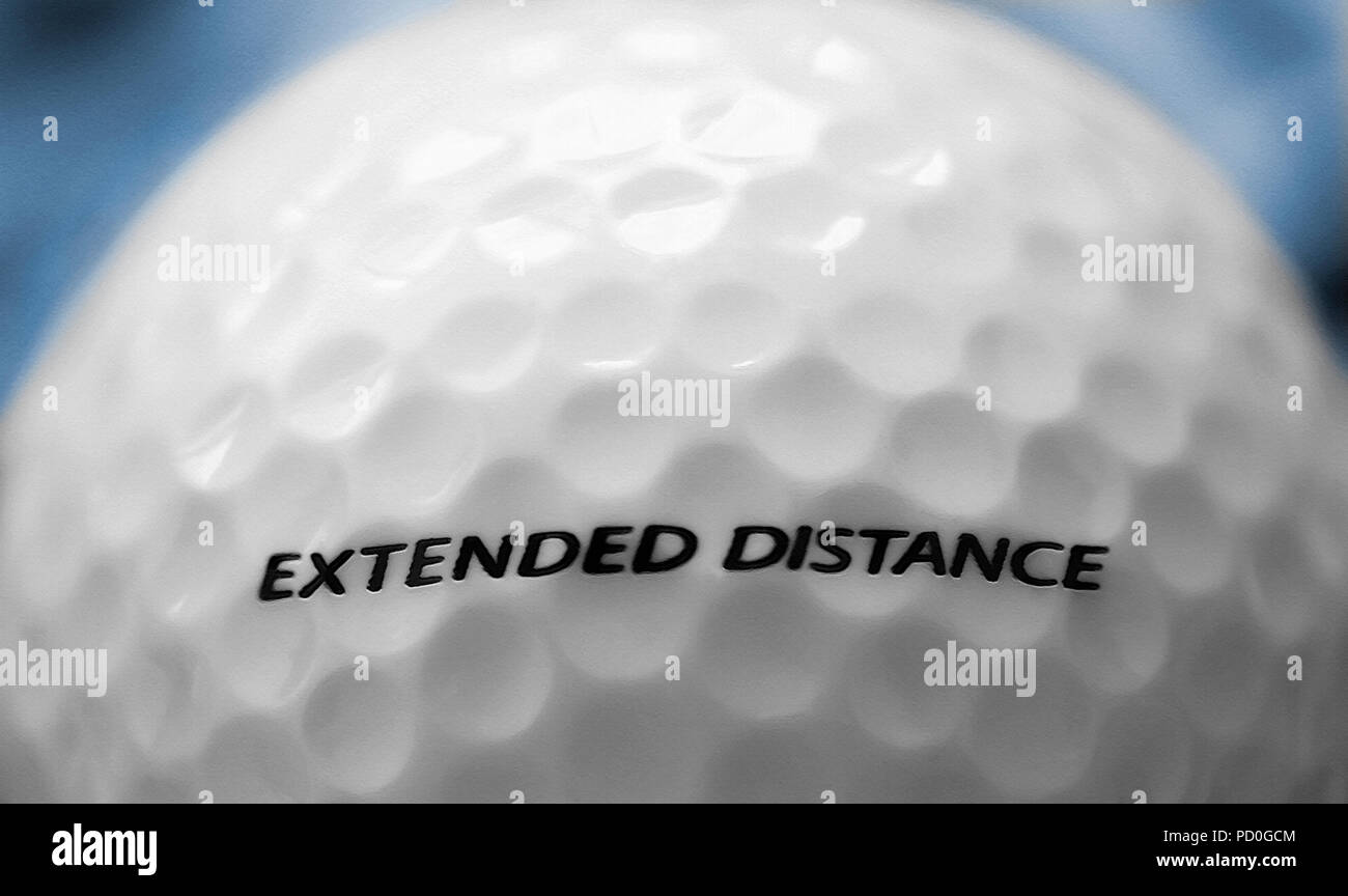 Macro image of a shiny new golf ball with the words 'Extended Distance' on the back side. Good motivational or conceptual usage. Original photograph h - Stock Image