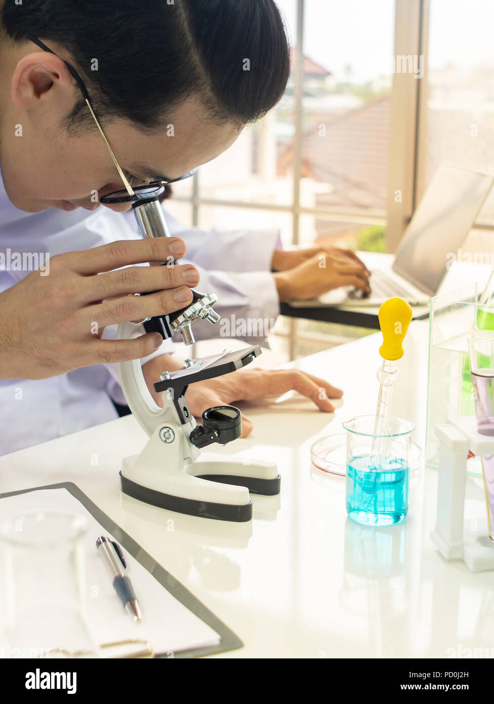 Asian male scientist,wearing eyeglass, analysing something through a microscope in a laboratory with female assistant working with computer in backgro - Stock Image