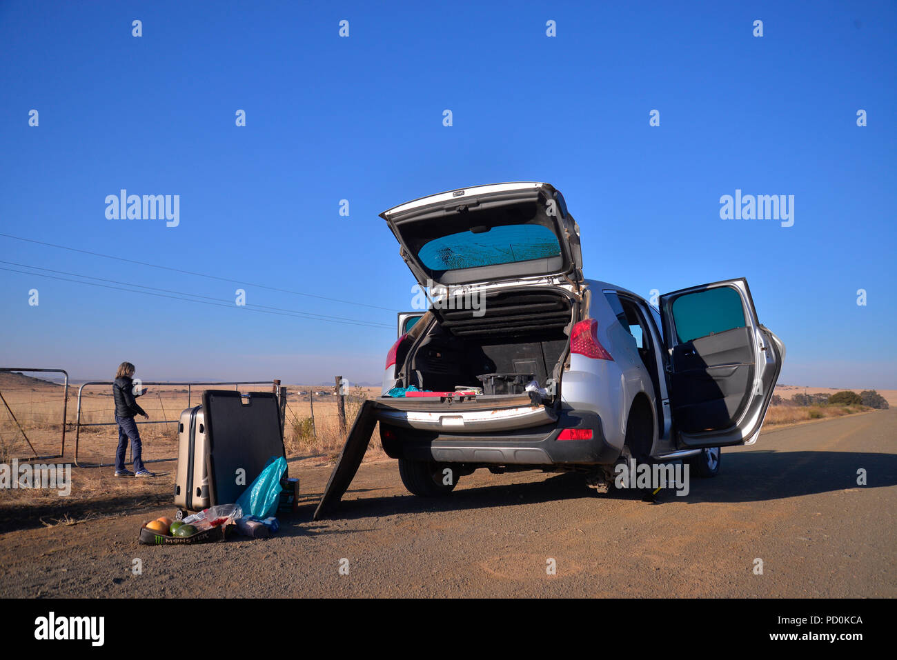 South Africa. Breakdown in the countryside. Car stranded in road. Woman using cell phone for help. Cases unpacked in road. - Stock Image