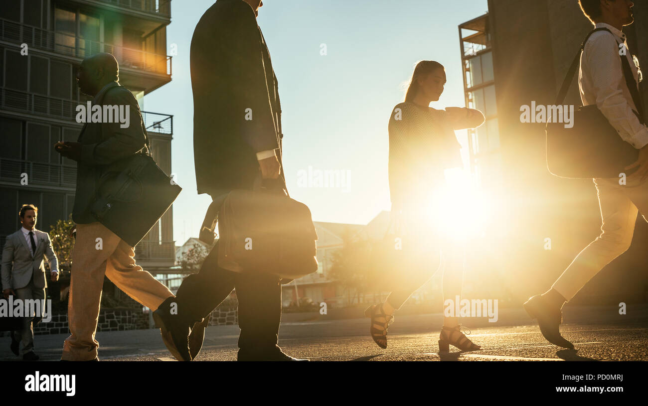 Men and woman commuting to office early in the morning carrying office bags with sun flare in the background. Businesswoman walking on a busy city str - Stock Image