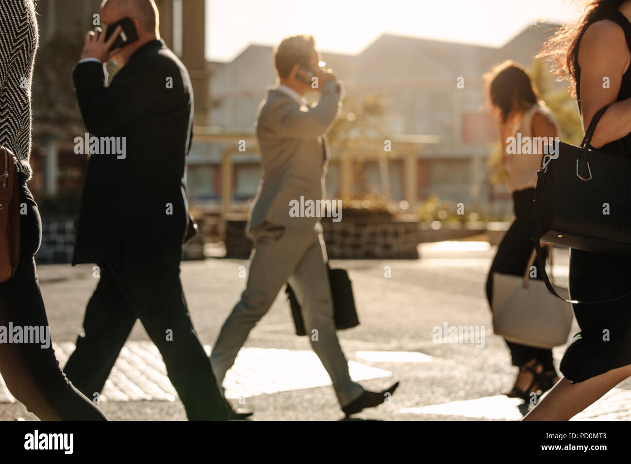 Men and women using mobile phone while commuting to office on a crowded street with sun flare in the background. People leading a busy life using mobi - Stock Image