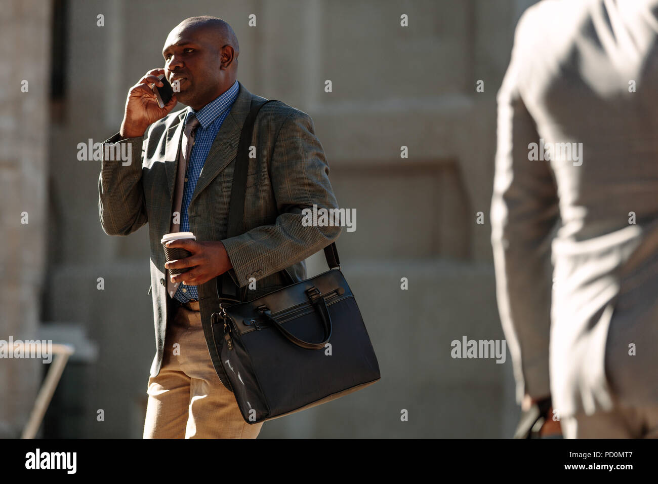 Businessman commuting to office talking over mobile phone with a coffee cup in hand with sun flare in the background. Busy man walking to office carry Stock Photo
