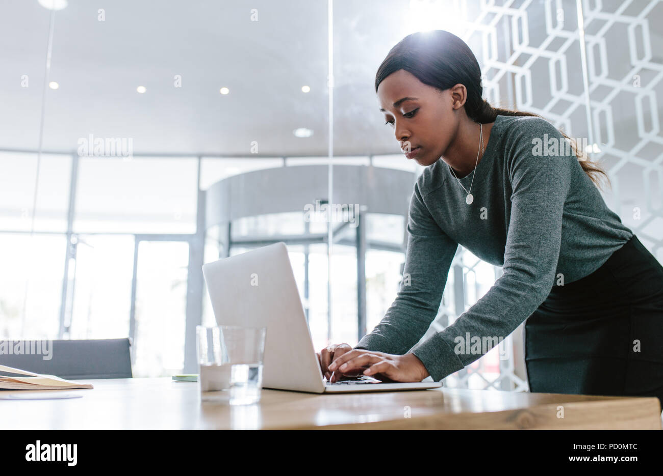 Young woman standing by conference table and working on laptop. Female preparing a business proposal before a meeting in boardroom. - Stock Image