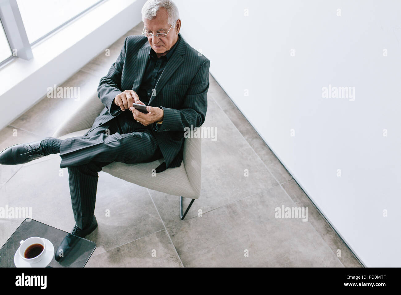 To view of old businessman using with mobile phone in office lobby. Mature corporate professional reading text message on his smartphone during break. - Stock Image