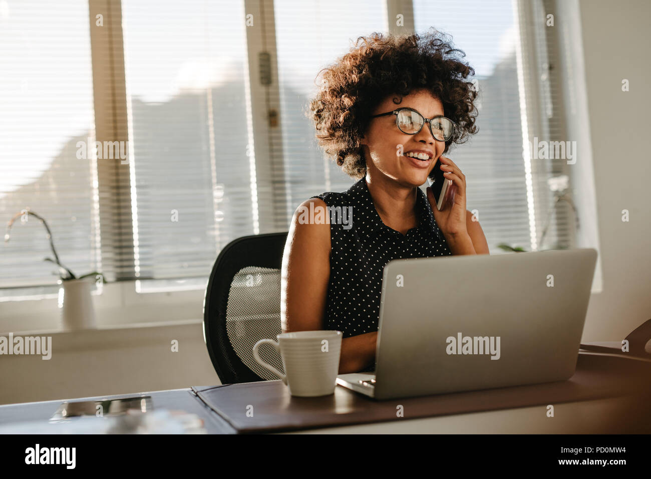 Young african woman working at her desk with laptop and talking on phone. Female wearing casual attire working at a startup office. - Stock Image
