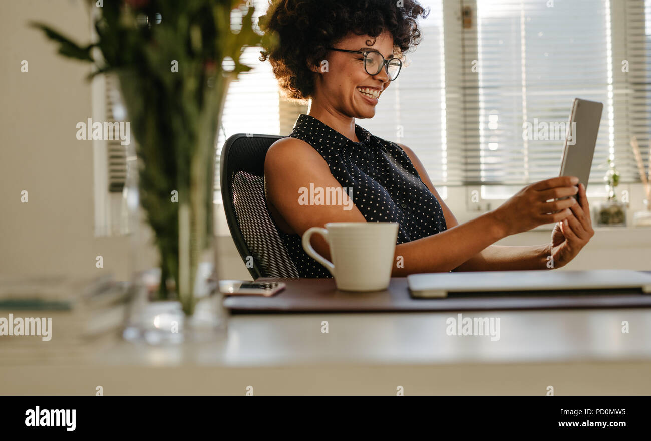 Young smiling black businesswoman sitting at her office desk and looking at the screen of the digital tablet in her hands. Happy young woman using dig - Stock Image