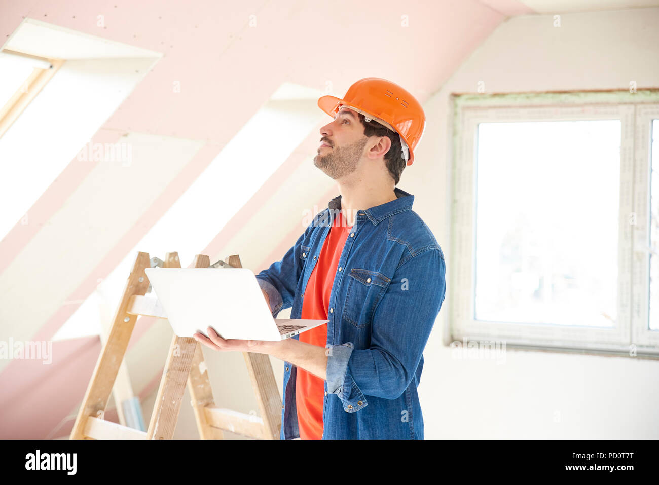 Shot of young engineer holding laptop in his hand while standing at construction site and working. - Stock Image