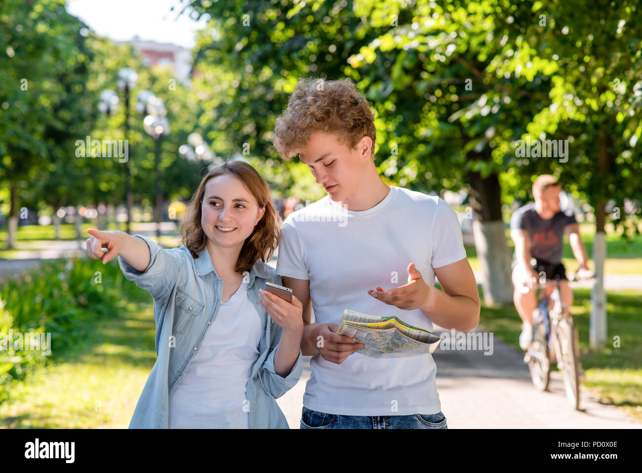 Boy and girl in summer in nature. Holds a roadmap and a smartphone. Indicates direction of movement. Travel around the city. A cyclist is passing by. Tourists in the city. - Stock Image