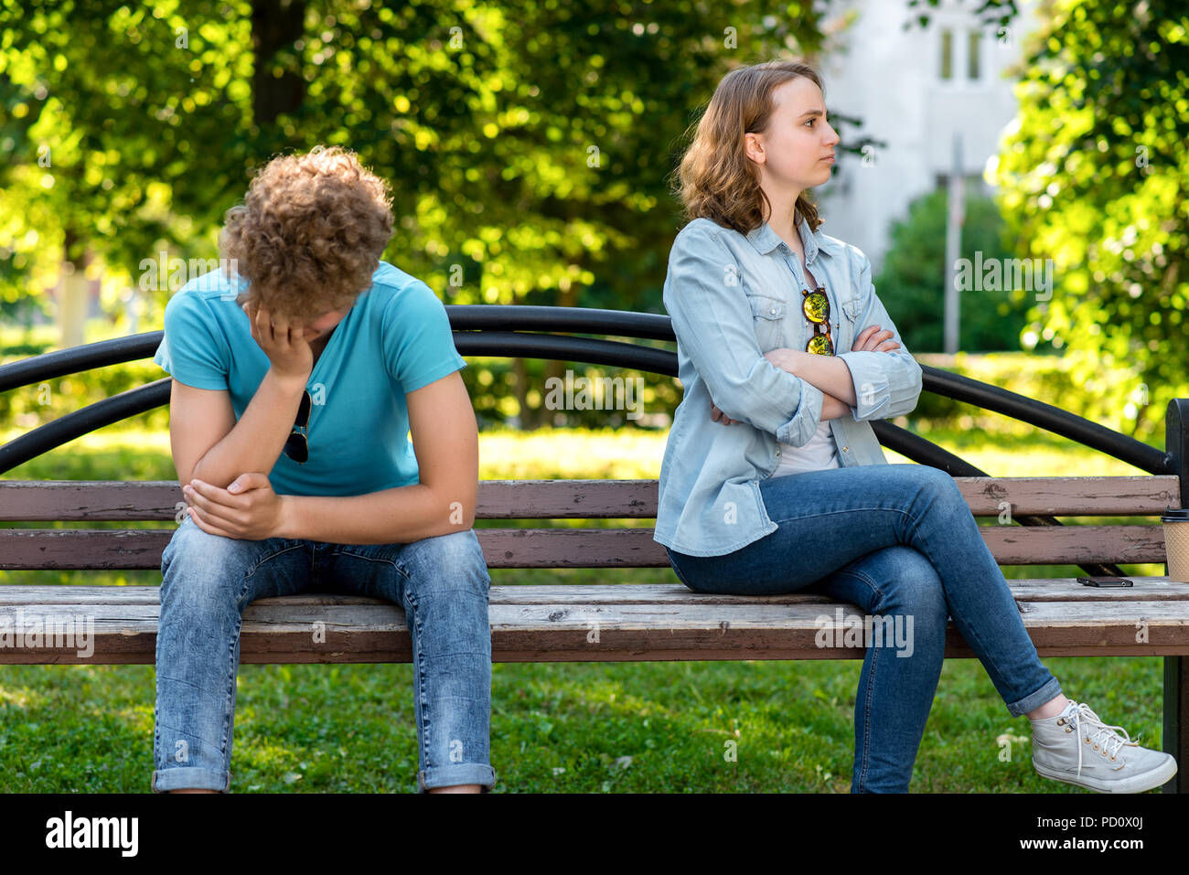 A boy and a girl sitting bench. In summer in park in nature. The concept resentment of misunderstanding. Quarrel in a relationship in street. Parting in a relationship. Unwillingness to listen. - Stock Image