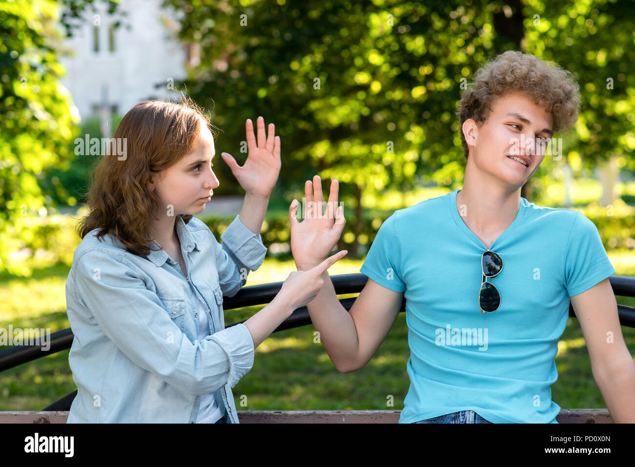 Young married couple. In summer in the park in nature. The girl rebukes the guy. Emotions of mistrust. Insults and insults in the relationship. Problems in family life. - Stock Image