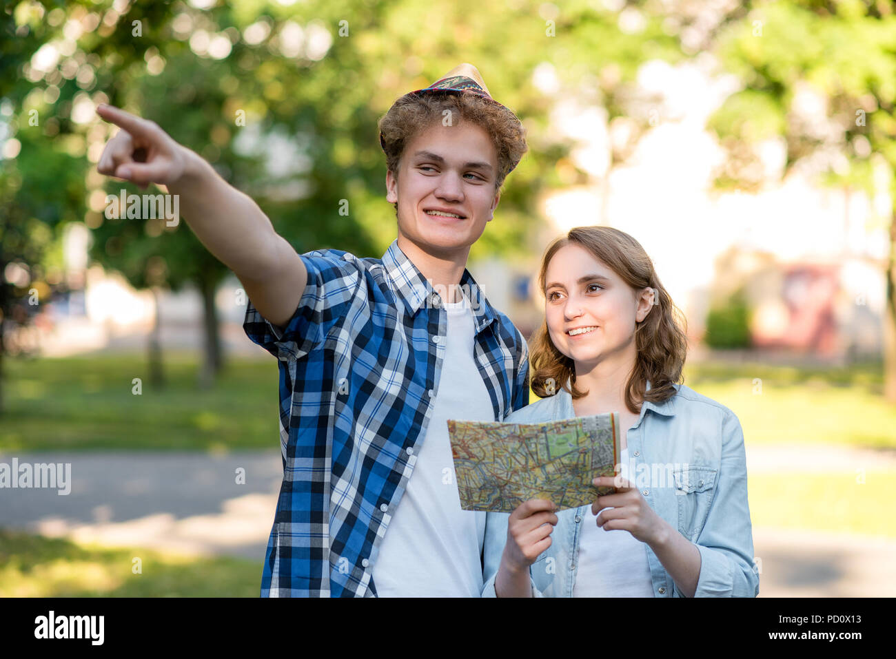 The guy with the girl smiles happily. In summer in the park in nature. In his hands holds a road map. With a gesture of the hand and shows the direction of movement. Young Tourists on vacation. - Stock Image