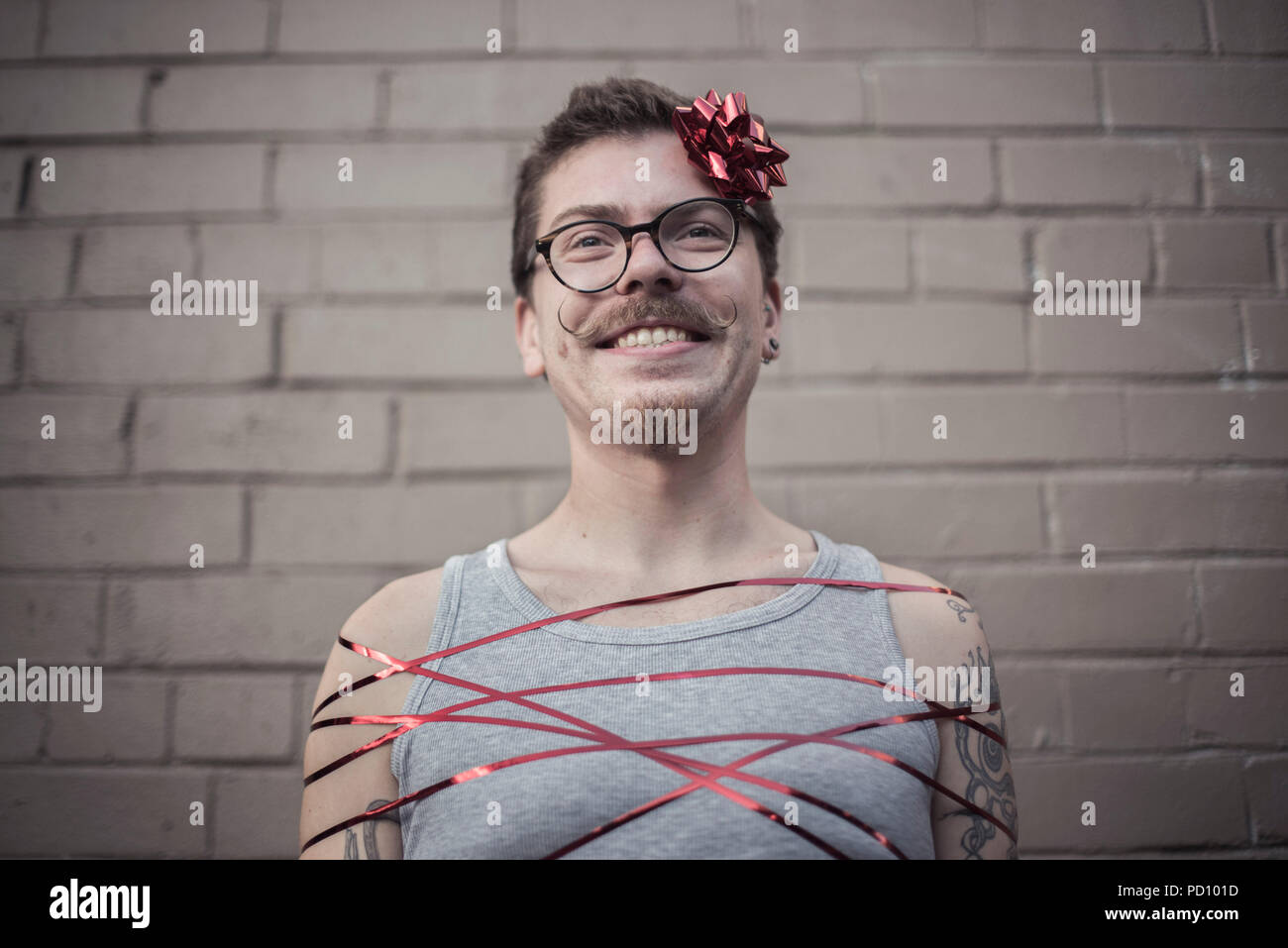 Young white man with tattoos wrapped in a red gift ribbon, with a red bow in the side of the head, curly moustache, and vintage glasses. Stock Photo