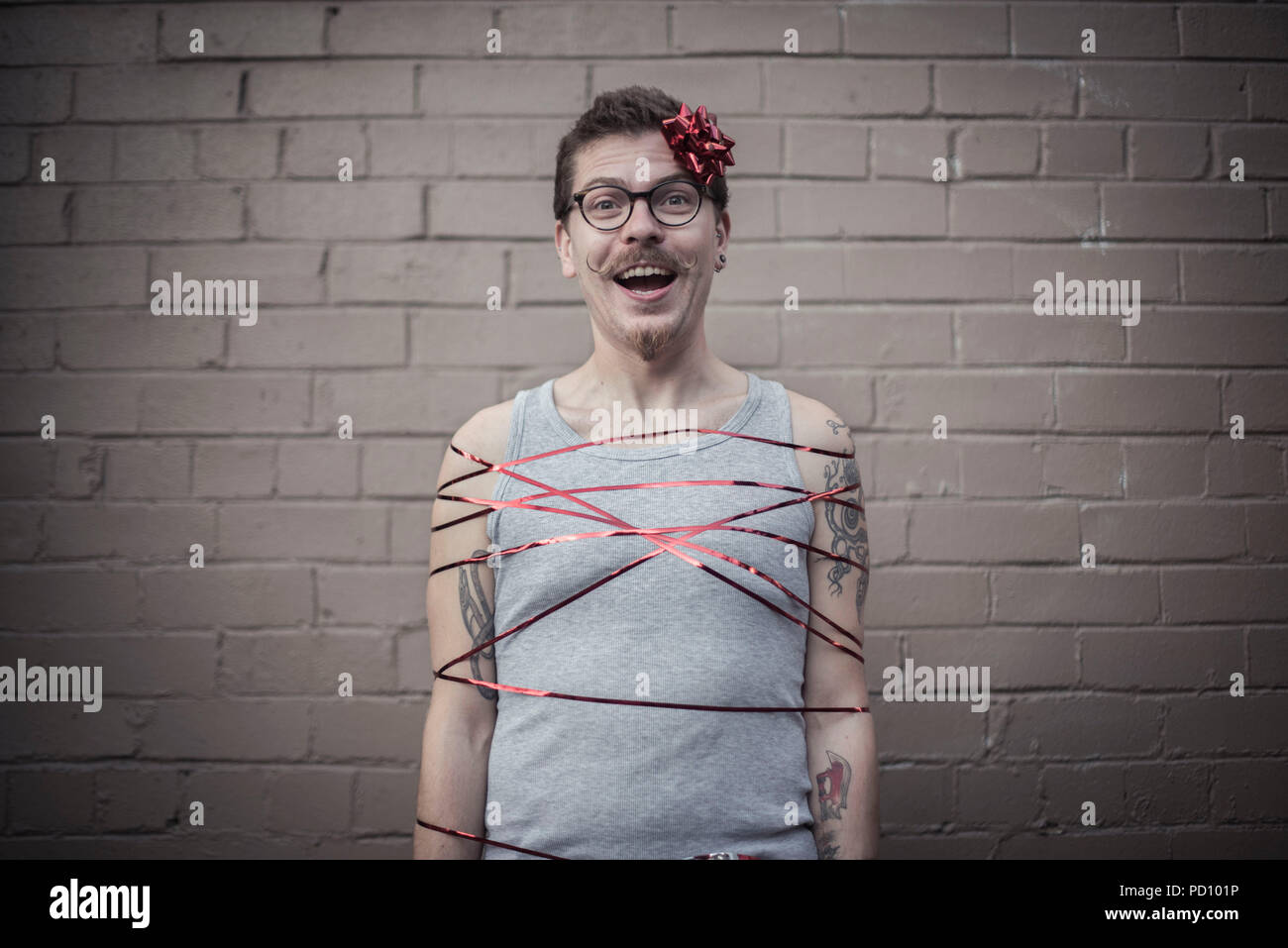 Young white man with tattoos wrapped in a red gift ribbon, with a red bow in the side of the head, curly moustache, and vintage glasses. - Stock Image