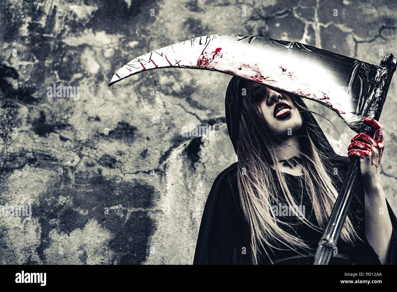 Demon witch licking blood on reaper. Female demon angel in black clothes and hood on grunge wall background. Halloween day and Mystery concept. Fantas - Stock Image
