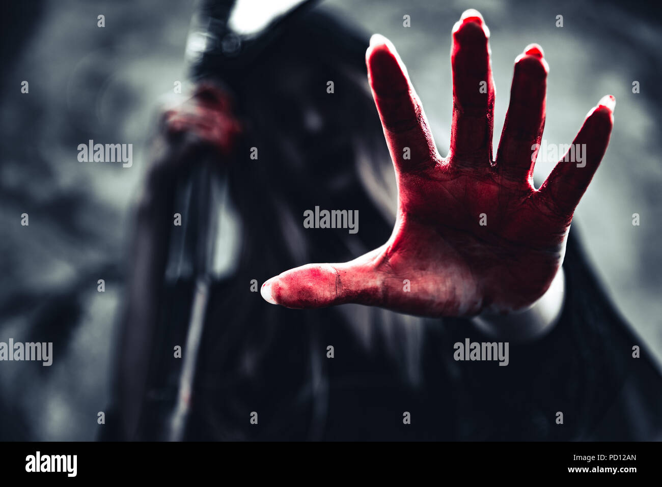 Witch showing bloody hand with reaper. Female demon angel in black clothes and hood on grunge wall background. Halloween day and Mystery concept. Fant - Stock Image