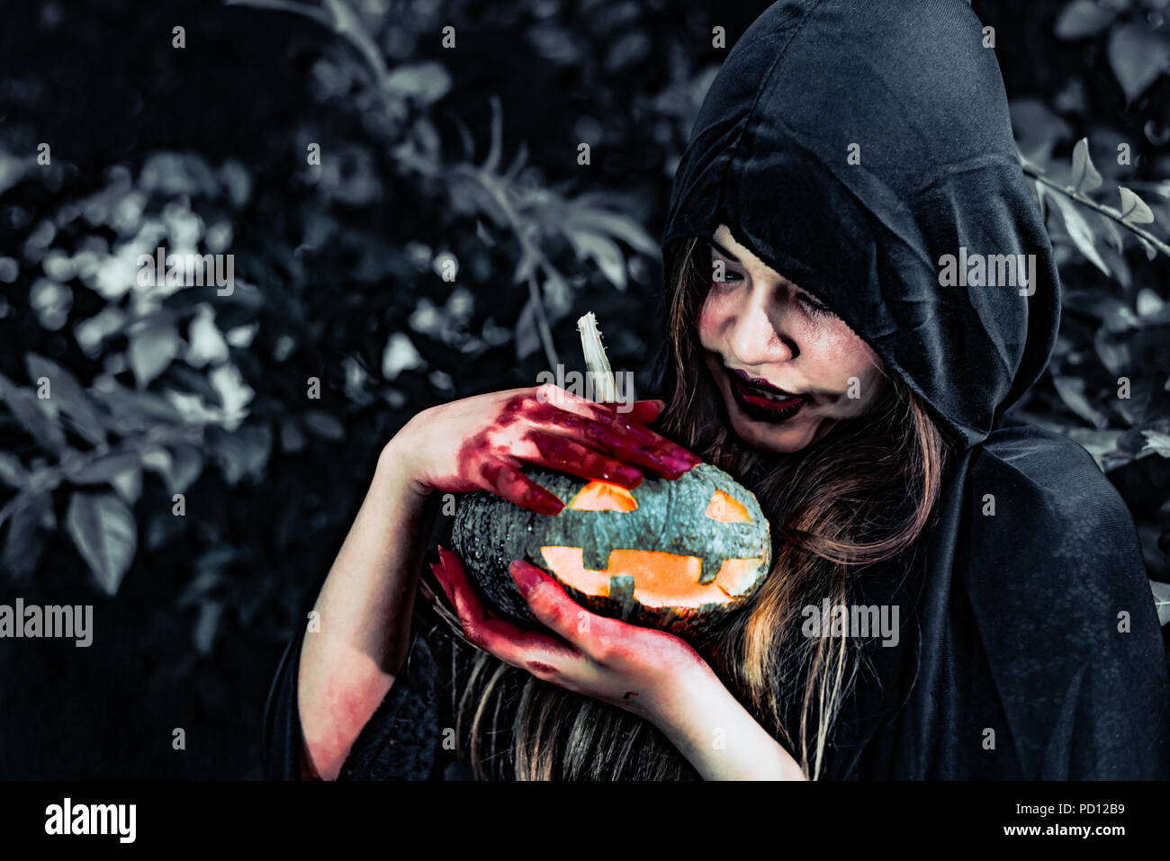 Demon witch take care of pumpkin in the mystery forest. Ghost and Horror concept. Halloween day theme. Red blood on witch hands. - Stock Image