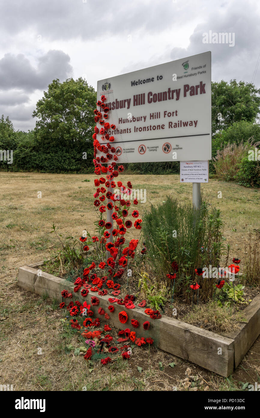 Sign for Hunsbury Hill Country Park garlanded with homemade poppies in remembrance of the centenary of the end of WW1; Northampton, UK - Stock Image