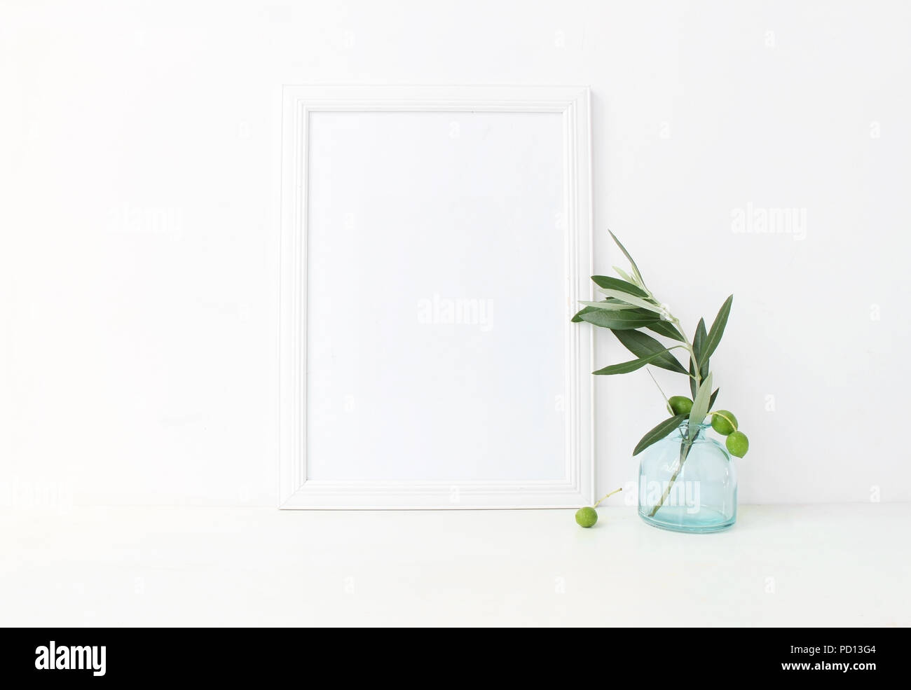 White vertical blank wooden frame mockup with a green olive branches in blue glass vase lying on the table. Mediterranean summer poster product design. Styled stock feminine photography. Home decor. - Stock Image