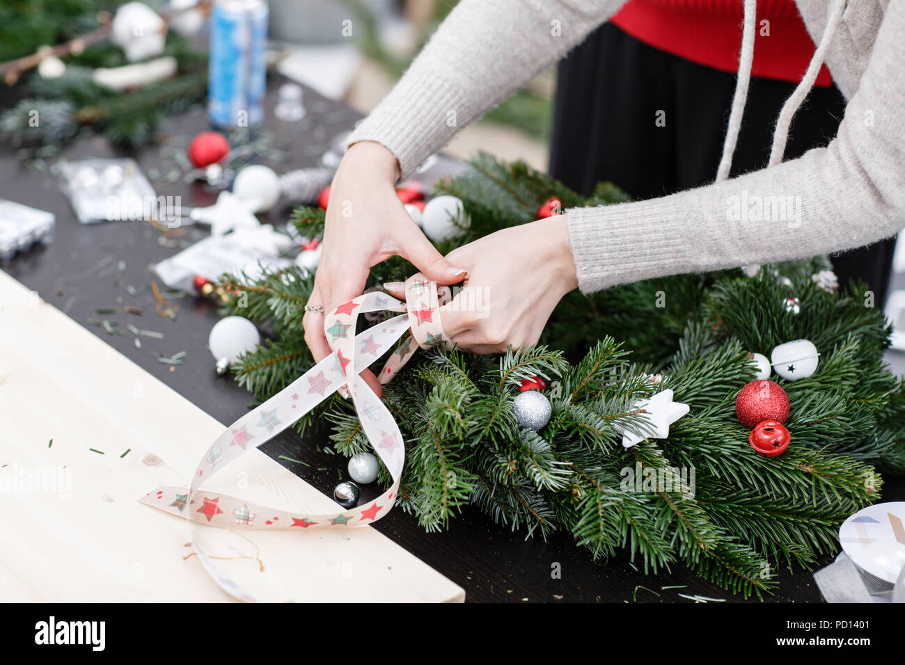 woman tying a bow ribbon decorated a christmas wreath attaches toys and decor with glue gun hands close up master class on making decorative ornaments - How To Tie Decorative Bows For Christmas Decor