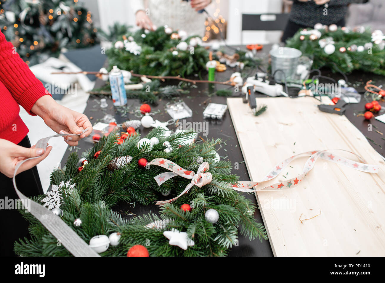 Woman tying a bow ribbon, decorated a Christmas wreath. Attaches toys and decor with glue gun. Hands close-up. Master class on making decorative ornaments. Stock Photo