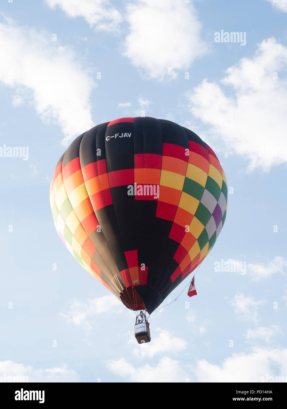 A Black, Red, Orange and Yellow Balloon with geometric pattern in Flight at the Big Sky Balloon Fest with the pilot and one passenger visible. - Stock Image