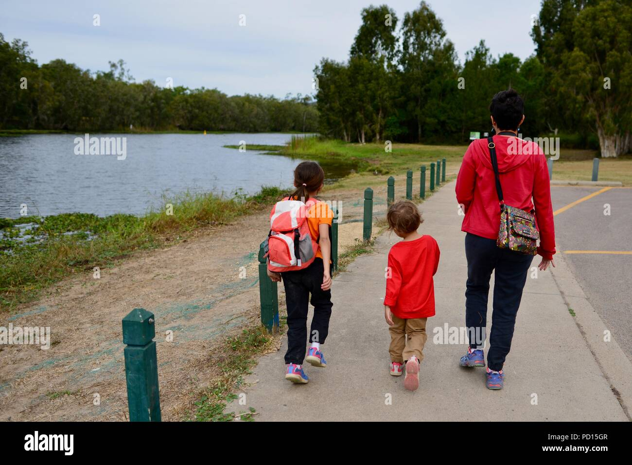 A woman and two children walk beside a river, Booroona walking trail on the Ross River, Rasmussen QLD 4815, Australia Stock Photo