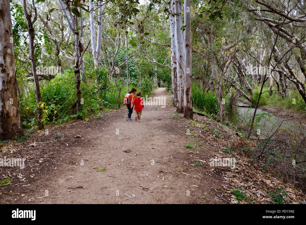 Two school age girls walking along a path, Booroona walking trail on the Ross River, Rasmussen QLD 4815, Australia - Stock Image