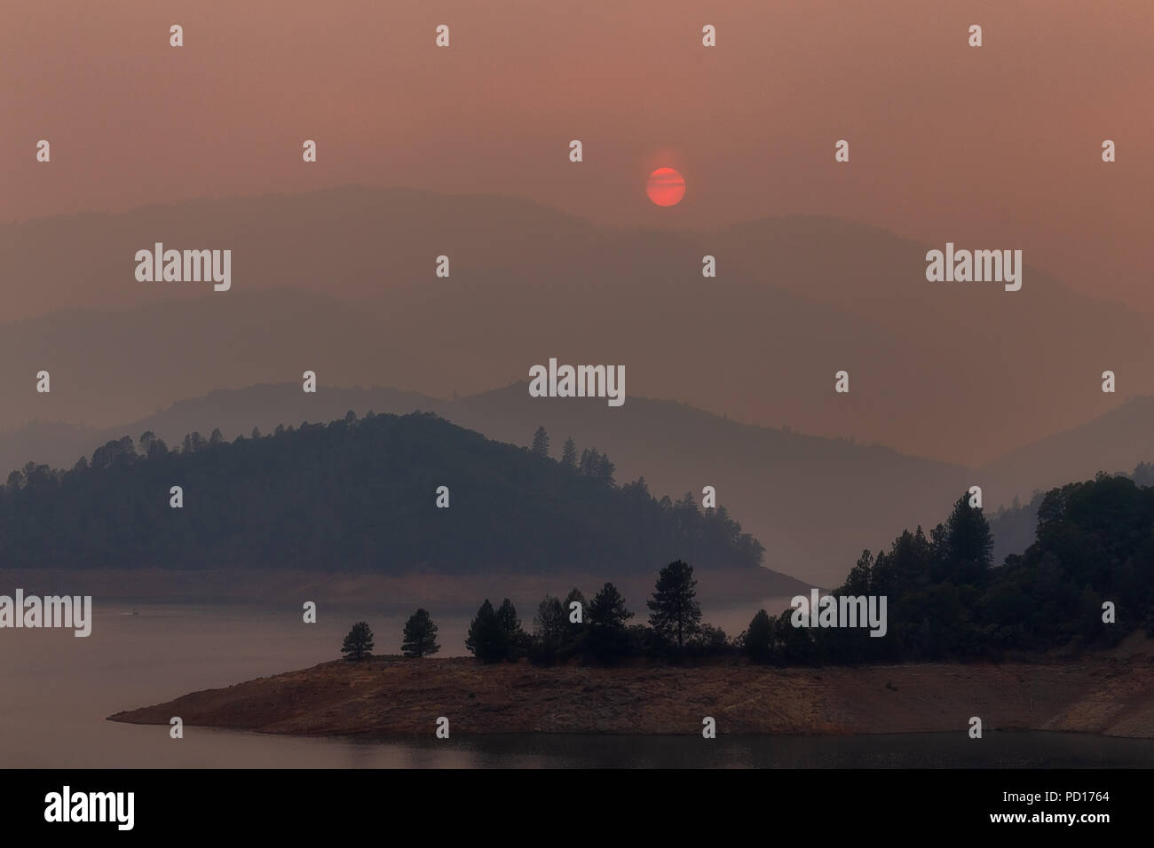 Wildfire smoke filled sky with setting sun over Shasta Lake during the Carr fire near Redding, California. - Stock Image