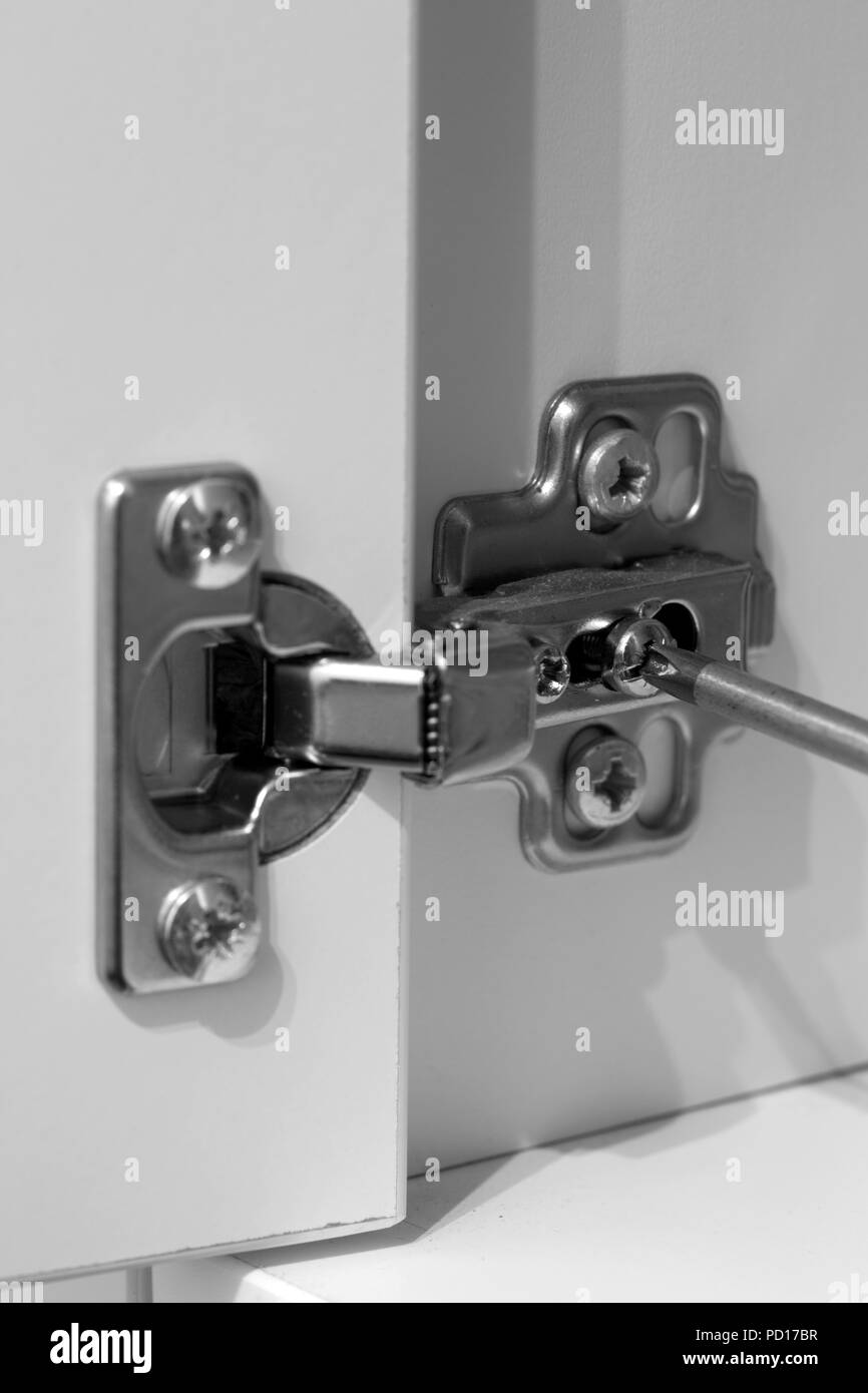Screwing hinge on a white cupboard to adjust the door with a screwdriver - Stock Image