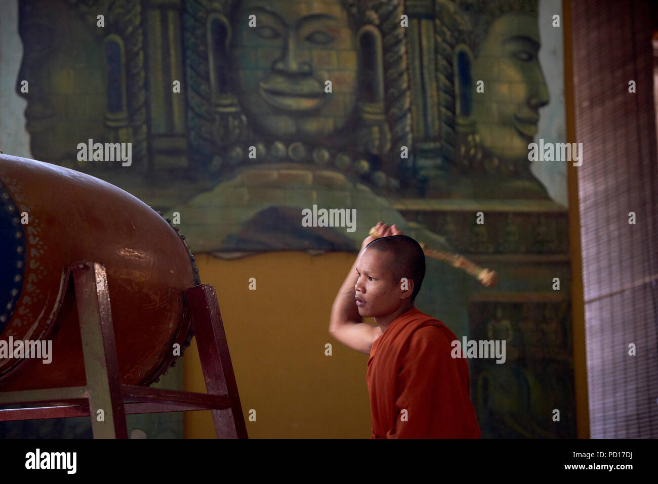 A young Buddhist monk playing a tambour during a ceremony at a monastery in Siem Reap, Cambodia, with faces of gods painted in a mural in the backgrou - Stock Image