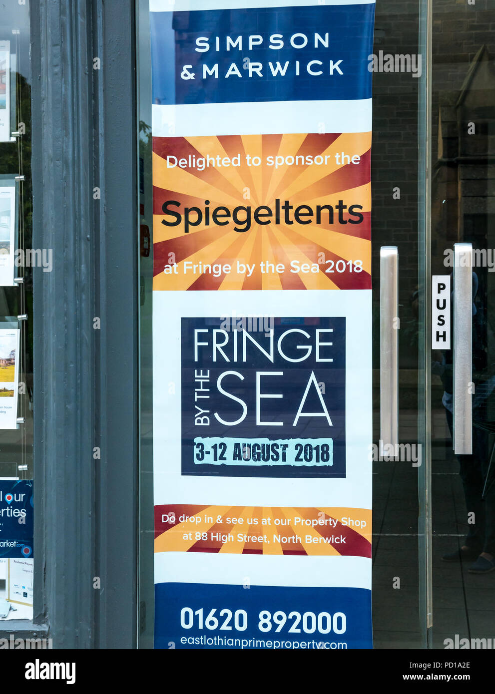 Fringe by the Sea Festival, North Berwick, UK. 4th August 2018. North Berwick, Scotland, United Kingdom:  Day 2 of the seaside festival, which complements the Edinburgh Fringe. Normally a week long, the festival runs for 10 days this year and features top comedians, writers, musicians, artists and bands. The Spiegeltents in the harbour are sponsored by estate agents Simpson & Marwick and appropriately named after them. The door of the office of Simpson & Marwick on the High Street - Stock Image
