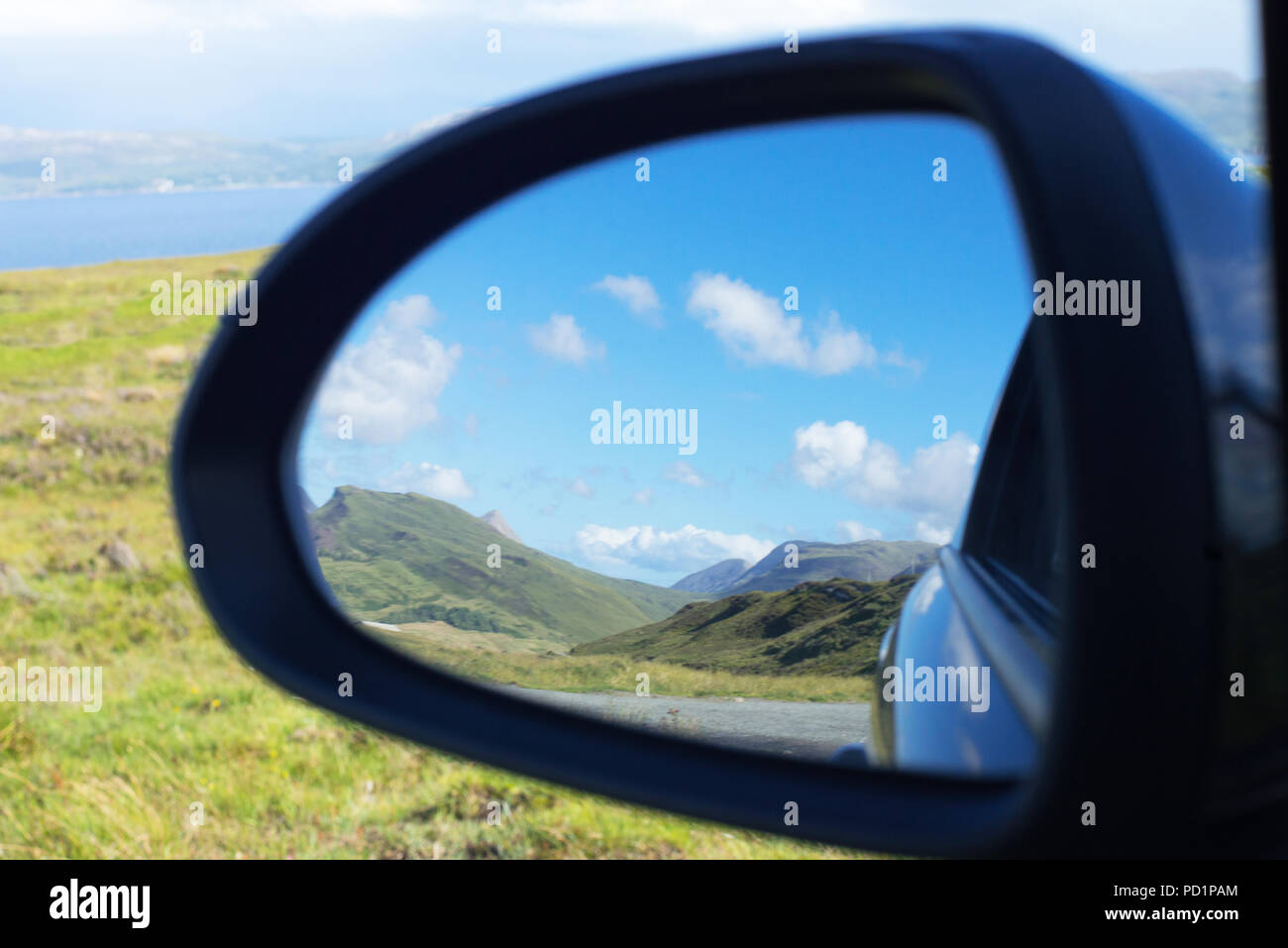 Cuillin Mountain range seen through the rear view mirror of a car in Isle of Skye, Scotland - Stock Image