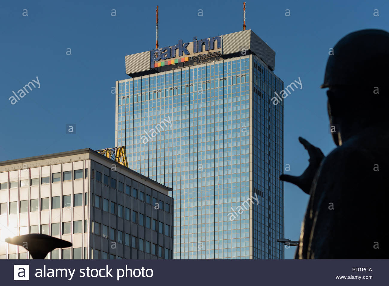 Hotel Park Inn in Alexanderplatz, center of Berlin. Shot on a sunny day under blue sky and behind a statue of a man rising  his and to the sky - Stock Image