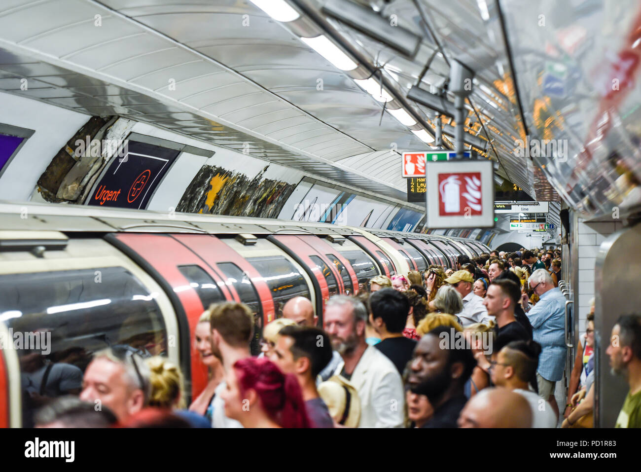 Crowded London Underground station platform and train, Tottenham Court Road tube station busy with passengers at peak time. Packed - Stock Image
