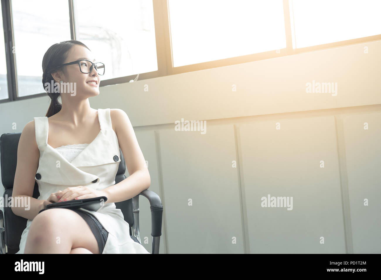 Young business woman in white dress who is candidate sitting wait for interview while looking out of big window. - Stock Image
