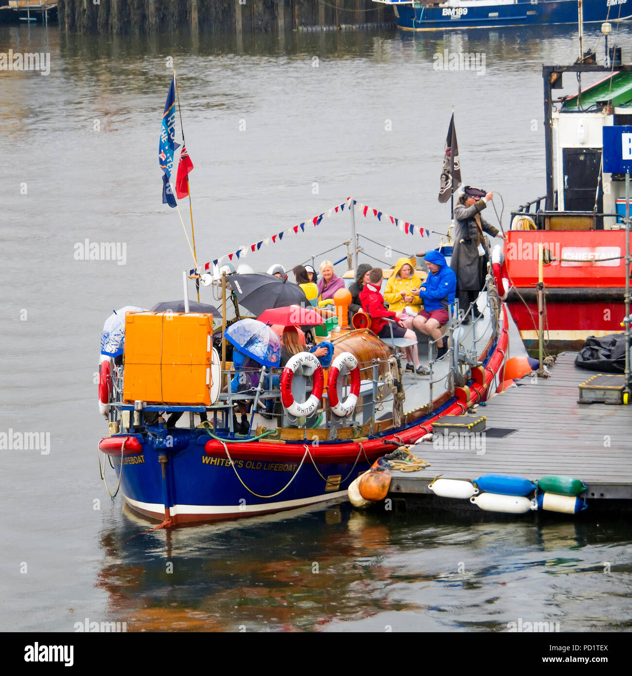 """Passengers on the old Whitby Lifeboat """"Mary Ann Hepworth"""" in Whitby harbour waiting to go on a summer pleasure trip  umbrellas up in heavy rain Stock Photo"""