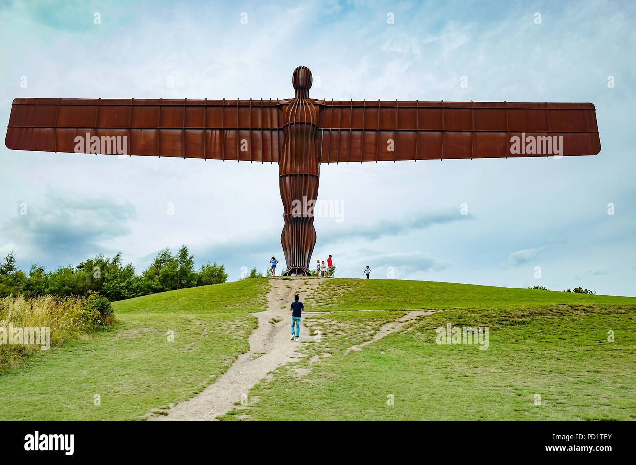 A group of people at the foot of the massive Angel of the North sculpture by Anthony Gormley  at Gateshead giving scale Stock Photo