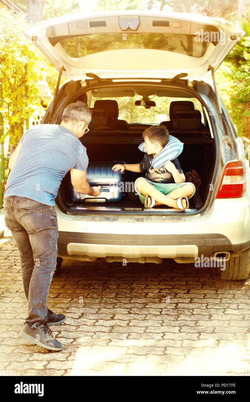 Little kid boy sitting in car trunk just before leaving for trip Stock Photo